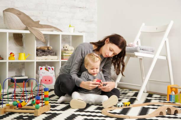 mamá y su bebé pasar tiempo juntos en la sala vivero - niñera fotografías e imágenes de stock