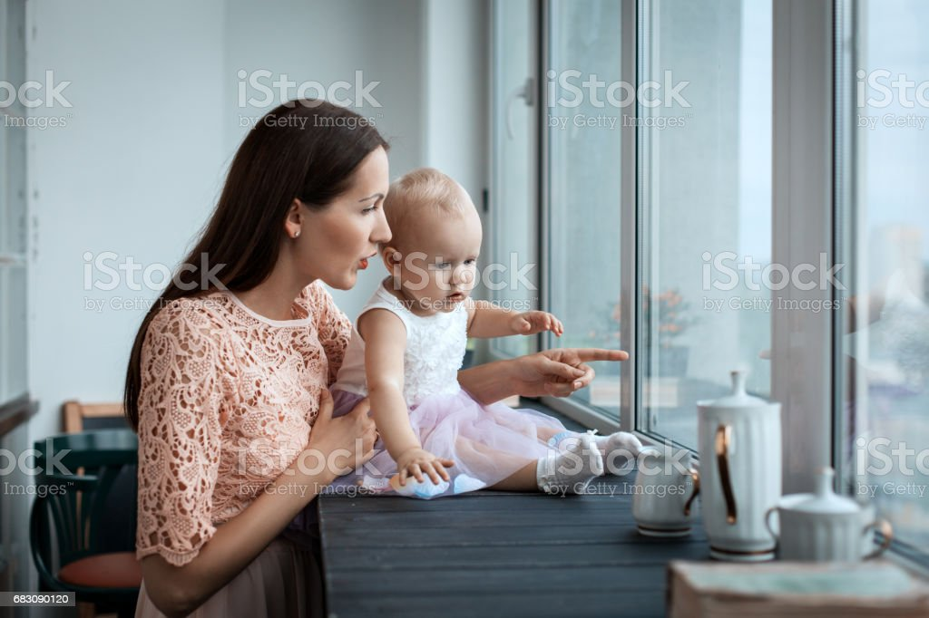 Mom and her daughter near the window foto de stock royalty-free