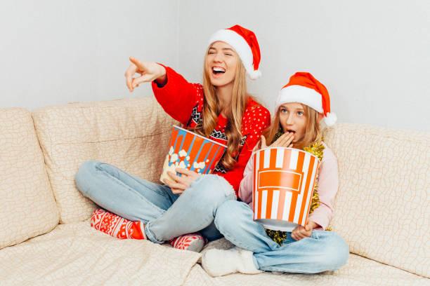 mutter und ihrer kleinen tochter, gekleidet im weihnachtsmann-mützen, filme schauen und popcorn essen, beim sitzen auf der couch. - kinder weihnachtsfilme stock-fotos und bilder