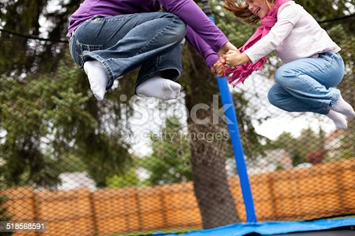 Color image of a happy girl jumping on a trampoline with her mommy during their home school gym class.