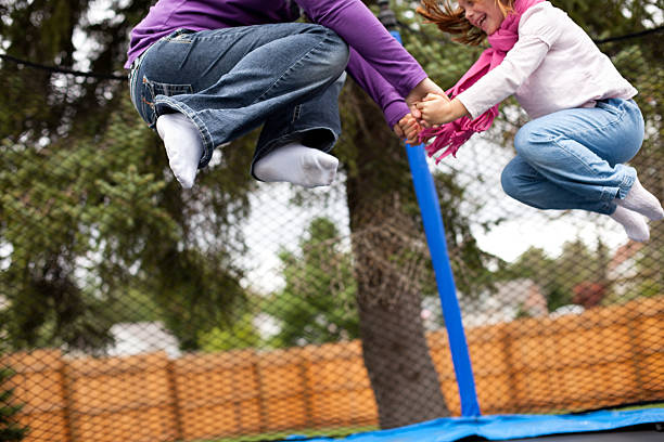 Mom and Her Little Girl  Jumping Together on Trampoline stock photo
