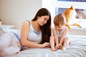 Mom and her toddler son plays with toy car at bedroom