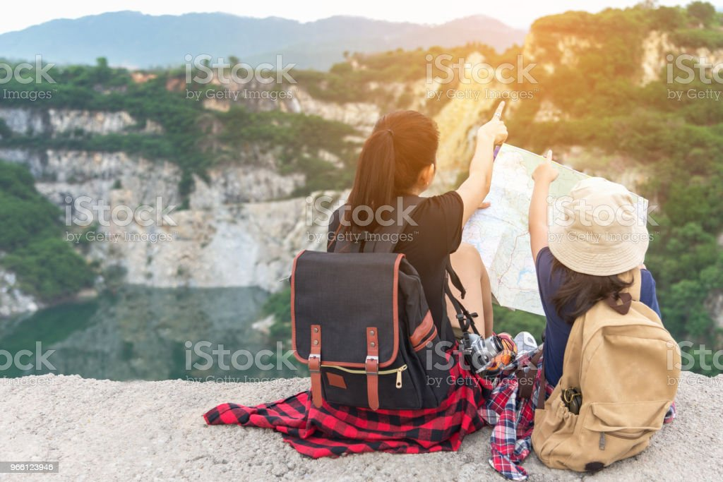 Mutter und Kind hält Karten und Reiserucksäcke sitzen siegreich mit Blick über den Grand Canyon für Bildung Natur. Reisekonzept - Lizenzfrei Abenteuer Stock-Foto