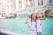 istock Mom and kid trowing coin at Trevi Fountain for good luck. Little girl making a wish to come back to Rome 655786542