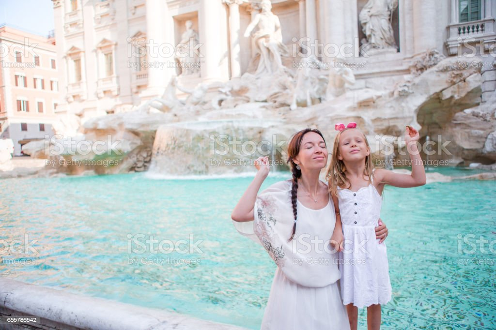 Mom and kid trowing coin at Trevi Fountain for good luck. Little girl making a wish to come back to Rome stock photo