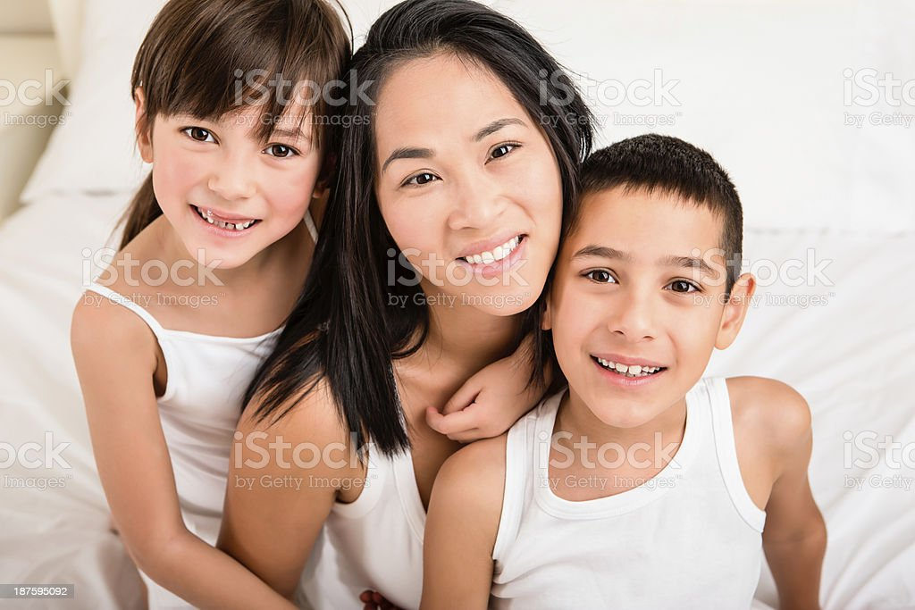 Mom and kids sitting in bed royalty-free stock photo