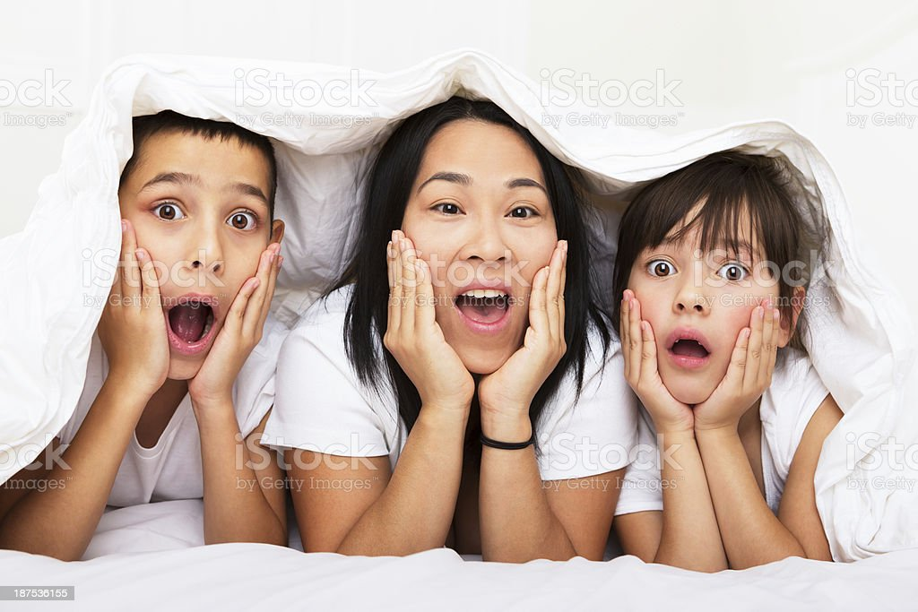 Mom and kids surprised, laying in bed royalty-free stock photo