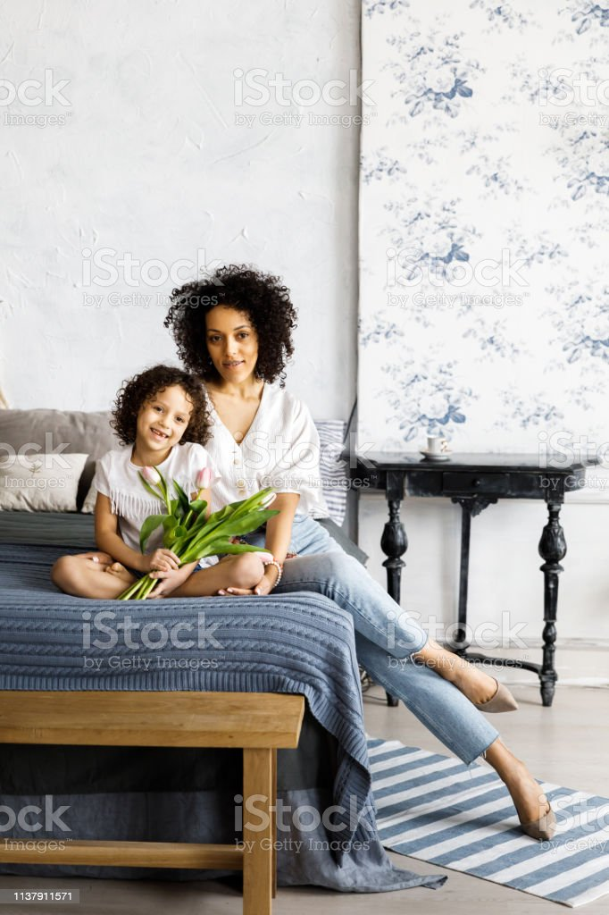 Mom and little cute curly girl sitting on bed with tulips in their...