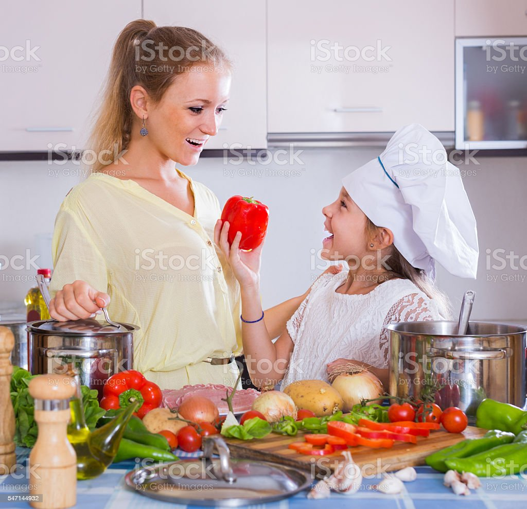 mom and little daughter cooking vegeterian dish indoors stock photo
