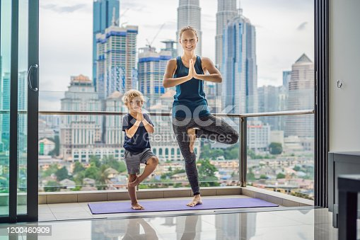 Mom and son are practicing yoga on the balcony in the background of a big city. Sports mom with kid doing morning work-out at home. Mum and child do the exercises together, healthy family lifestyle concept.