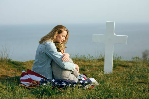 mom and son are sitting on the grave of a soldier. mom brought her son to the grave of his father on memorial day 27 may - family 4th of july zdjęcia i obrazy z banku zdjęć