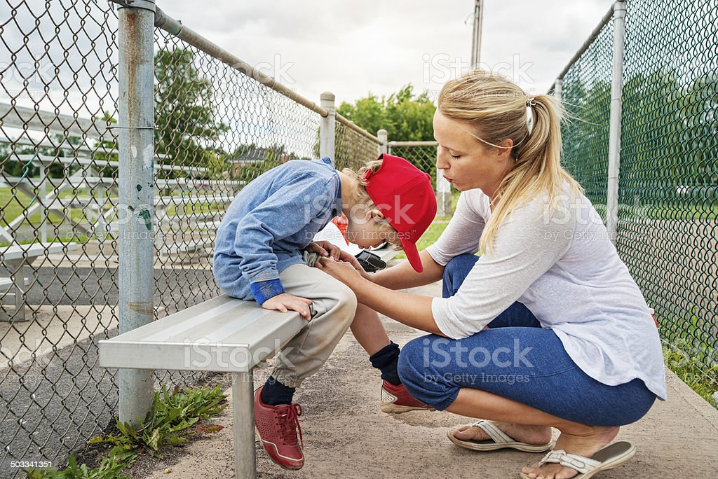 Mom and son blowing on scraped knee on baseball bench. stock photo