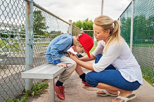 Mère et fils de souffler sur usé genou sur banc de baseball. - Photo