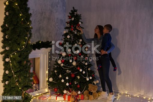 istock Mom and son Christmas tree Christmas tree gifts lights garlands 1218417627