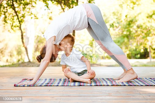 istock Mom and son do yoga in a summer park. Healthy lifestyle. 1200932578