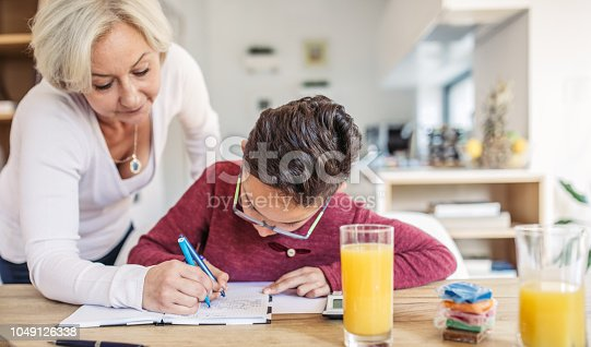 680535874 istock photo Mom and son doing homework at home 1049126338