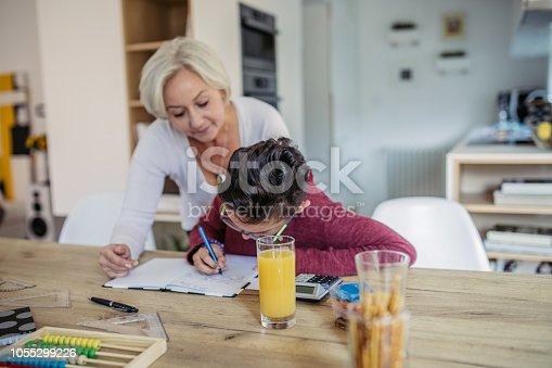 680535874 istock photo Mom and son doing homework 1055299226