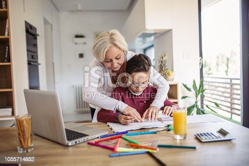 680535874 istock photo Mom and son doing homework together 1055714652