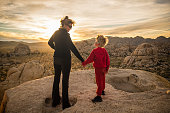 Mom and Son High Desert holding hands watching the sunset from on top of a rock formation.