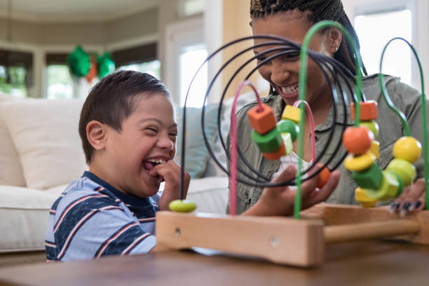 mom and son laugh together while playing in living room - handicapped imagens e fotografias de stock