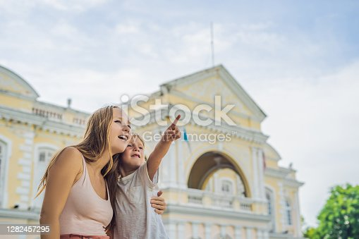 Mom and son on background of Old Town Hall in George Town in Penang, Malaysia. The foundation stone was laid in 1879.