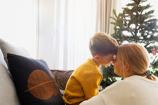 A mom and son are hugging, cuddling, and feeling the Hollyday spirit next to the Christmas tree.