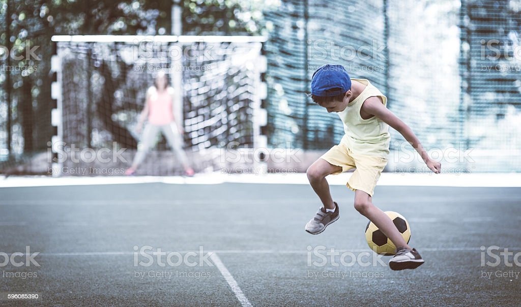 Mom and son playing football on stadium royalty-free stock photo