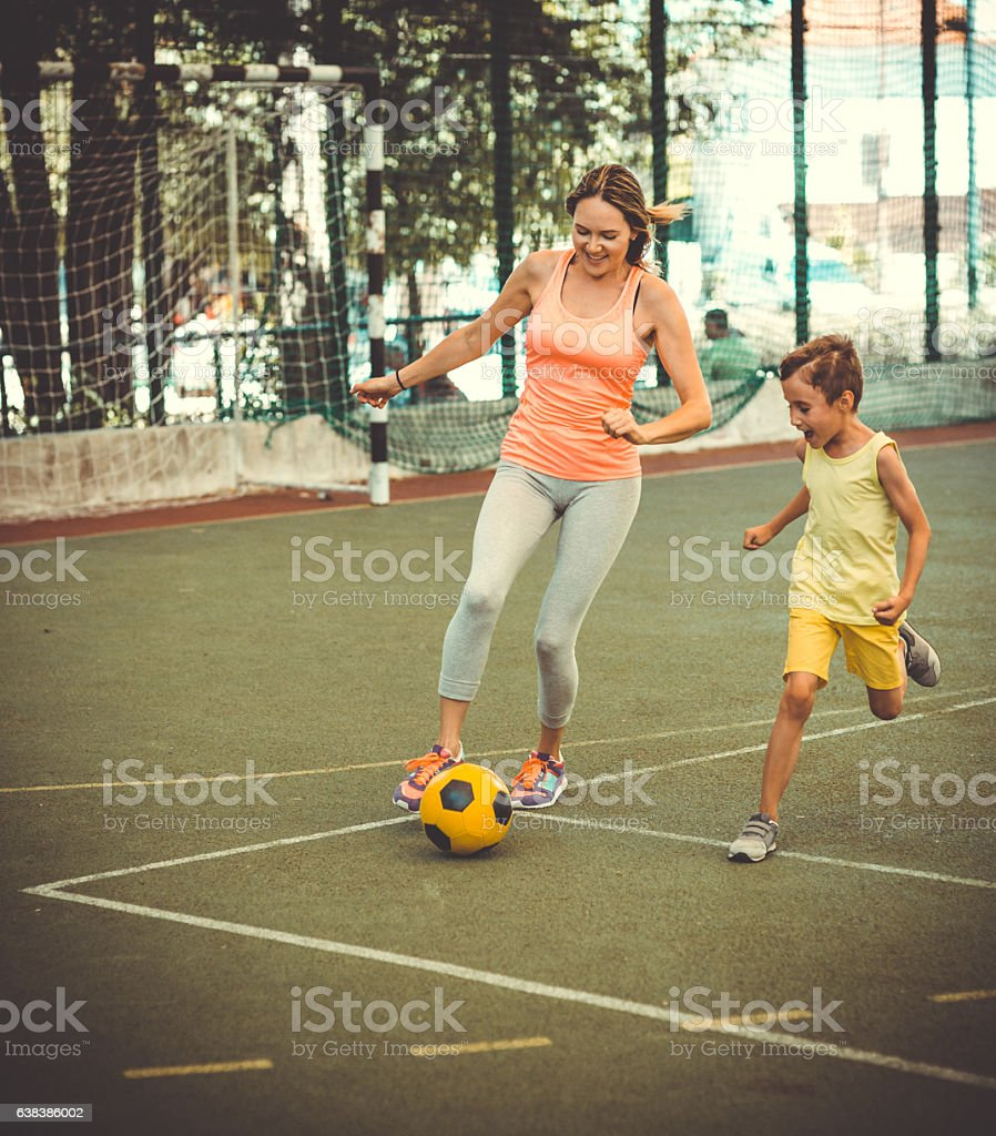 Mom and son playing football on stadium stock photo
