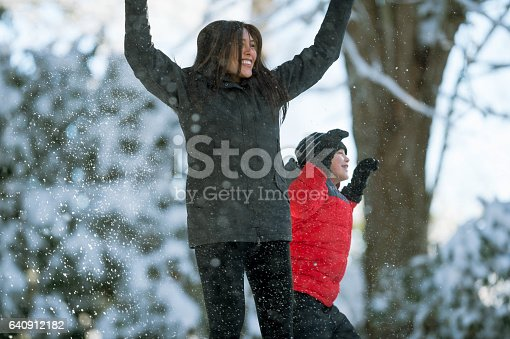 Mom and son playing in snow together.
