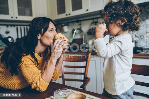 Mom and son playing in the kitchen, drinking tea