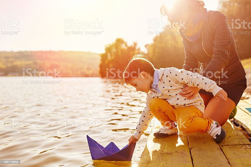 Mom and son playing with paper boats by the lake stock photo
