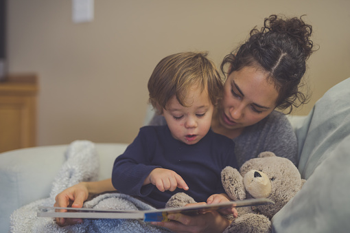 Young Hispanic mom reads a book aloud to her young son, who has food on his face.. They're pointing at the pictures together. A teddy bear is snuggled up with them.