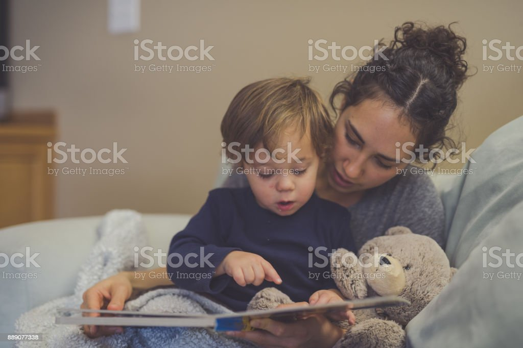 Mom and Son Reading Book Together in Living Room stock photo