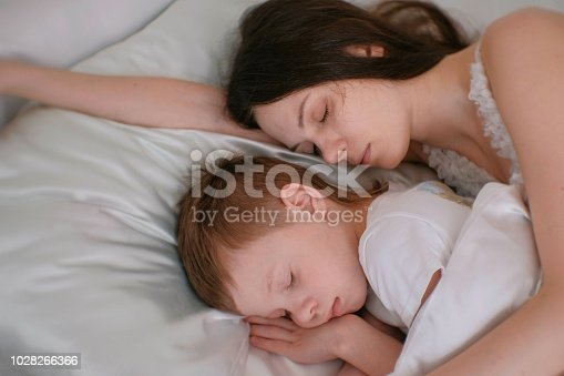 Mom and son sleeping together. Mom hugging her son