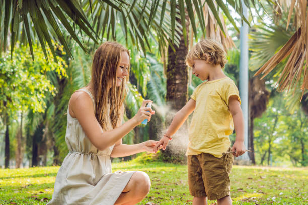 Mom and son use mosquito spray.Spraying insect repellent on skin outdoor Mom and son use mosquito spray.Spraying insect repellent on skin outdoor. ugliness stock pictures, royalty-free photos & images
