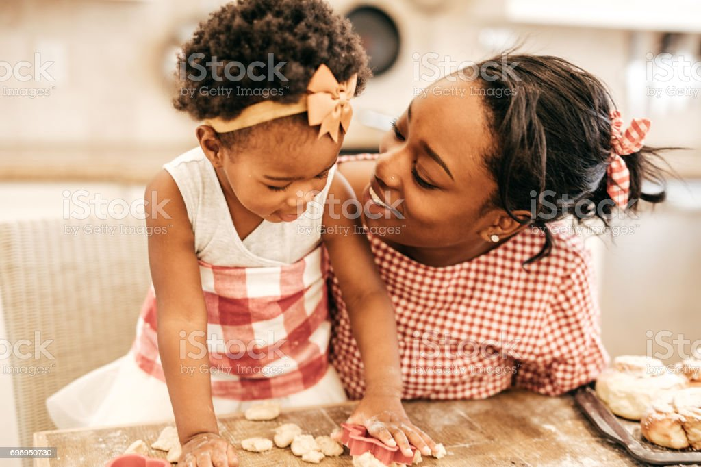 Mom and toddler baking together stock photo