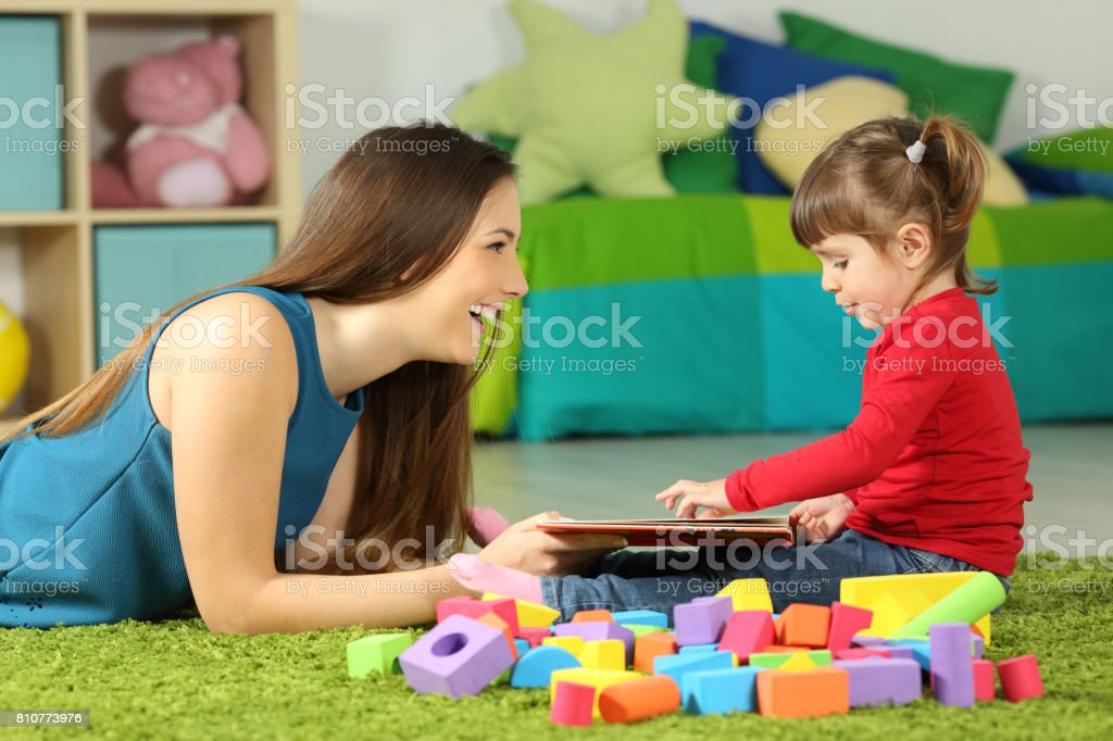 Mom and toddler playing with a book stock photo