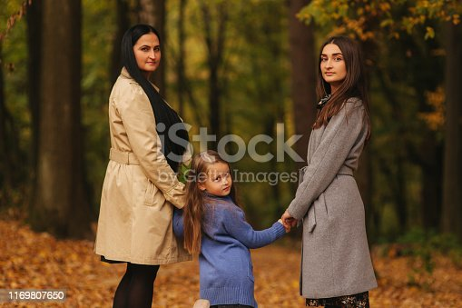 Mom and two daughter have fun in ther park. Youngest daughter collect leaves and smile. Happy family walking in the forest.