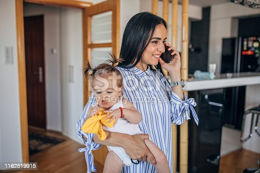 One woman and baby, single mother holding her daughter and talking on mobile phone.