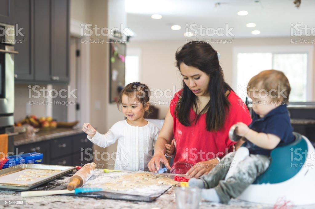 Mama backt mit ihren kleinen Kindern in einer modernen Küche – Foto