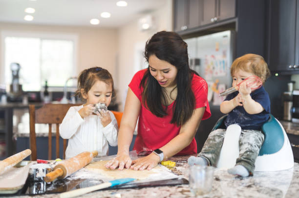 Mom baking with her children in a modern kitchen stock photo