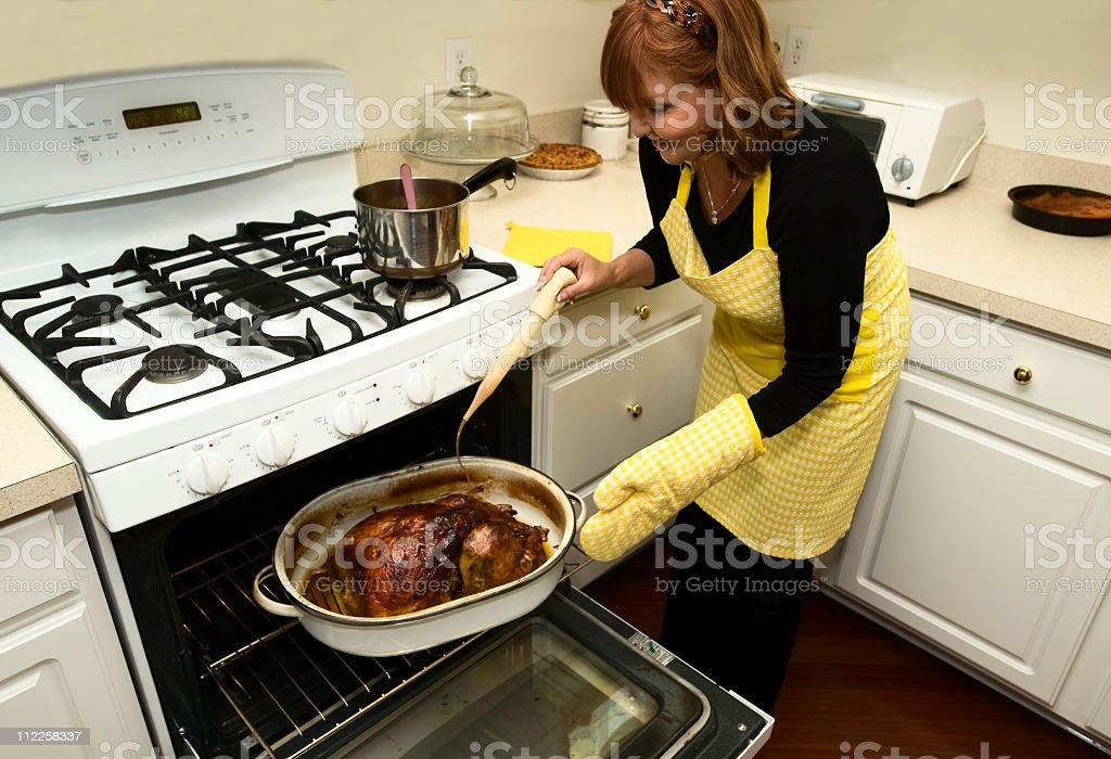 Mom Basting a holiday turkey royalty-free stock photo