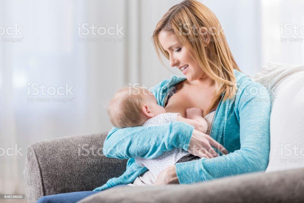 Hija de tomas de pecho de la mamá en casa - foto de stock