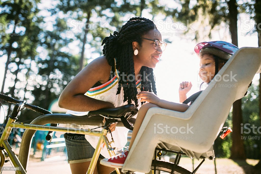 Mom Buckles Up Daughter in Bike royalty-free stock photo
