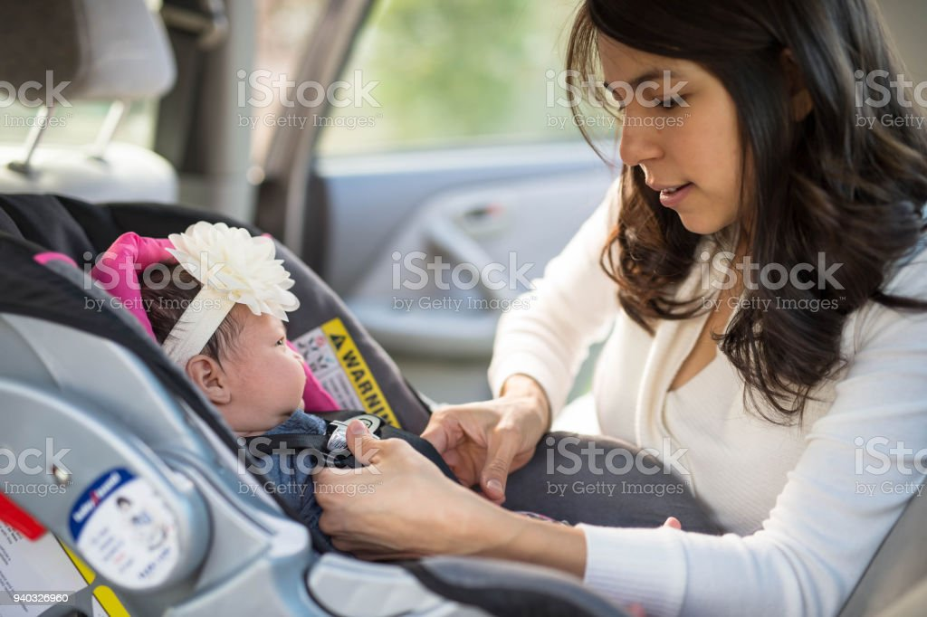 Mom Buckling Infant Into Car Seat stock photo