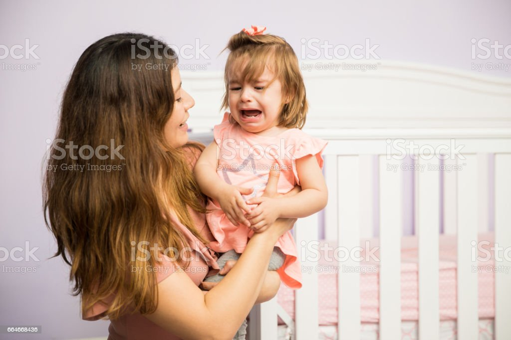 Mom calming down her crying daughter stock photo