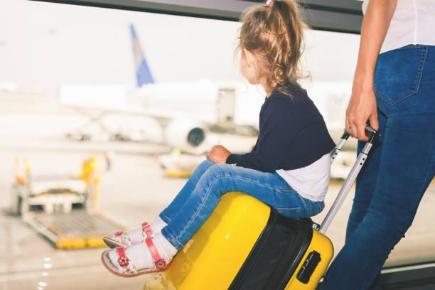 Mamá lleva su equipaje con bebé feliz en terminal del aeropuerto - foto de stock
