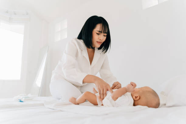Mom changing diaper for newborn baby stock photo