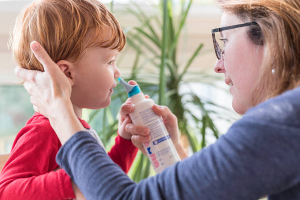Mom Cleans Baby's Nose With Blower and Saline Nasal Spray Mom Cleans Baby's Nose With Blower and Saline Nasal Spray saline drip stock pictures, royalty-free photos & images