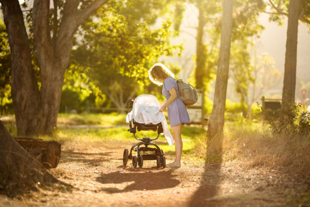 Mom covering her baby in a stroller while walking in a park stock photo